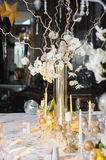 Festive table decorated with candles. The branches of orchids in vases on the holiday table. Decorative branch with crystal elements decorated table Royalty Free Stock Photo
