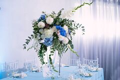 the festive table is decorated with vase of flowers, table decor with a gardenia, a wedding celebration, a blue tablecloth,