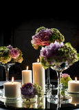 Festive table decoration. With candles and bouquets of flowers Stock Images