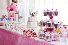 Festive table decorations with cupcakes, sweets and gifts in pink color stock photos