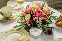 Festive table with flower bouquet and porcelain dining set. Festive table with flower bouquet and luxury porcelain dining set with gold royalty free stock image