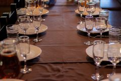Festive table with glass glasses and white plates. On the big table stock images