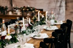 Festive table served for wedding or birthday. Beautiful cutlery, candles, luxurious chairs and table. Elegant dinner table. Party royalty free stock images