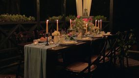 Festive table with serving, cloth, croissants, candles, macaroons, flowers.