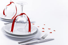 Festive table set with glasses with hearts on white background h. Wine glasses turned upside down with red decoration as background for invitation and menu Stock Images
