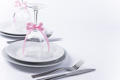 Festive table set with glasses and silverware on white backgroun. Wine glasses turned upside down with pink decoration as background for invitation and menu Stock Photos