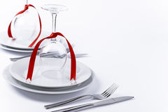 Festive table set with glasses and silverware on white backgroun. Wine glasses turned upside down with red decoration as background for invitation and menu Stock Image