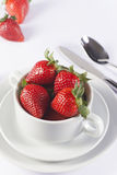 Festive table set with strawberry in bowl on white background. Fresh strawberry in white soup bowl for menu and invitation Stock Photography