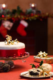 Festive Table Setting. With Christmas cake and mince pies, decorated fireplace in background with lit candles Royalty Free Stock Photos