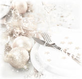 Festive table setting. Photo of luxury festive table setting, beautiful white dishware decorated with silver baubles and candles, elegant plate served with knife Royalty Free Stock Photo