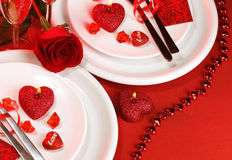 Festive table setting. Picture of luxury festive table setting, white plate on red tablecloth served with silverware cutlery and decorated with fresh rose flower Stock Photos