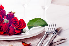 Festive table setting with beige roses, wine glasses, napkins and cutlery, Stock Image