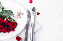 Festive table setting with beige roses, wine glasses, napkins and cutlery, Stock Photo