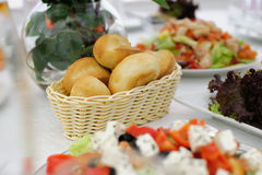 Festive table setting. Buns in a wicker basket. Banquet table, Serving dishes, Food restaurant.  Wedding evening. The peoples kitchen. A range of snacks. Decor Stock Photo