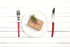 Festive table setting with cutlery and Christmas gift box on whi Stock Photo