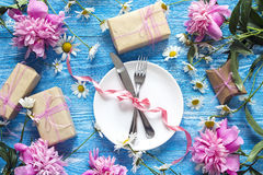 Festive table setting with cutlery, peonies and gift boxes on bl Royalty Free Stock Photo