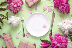 Festive table setting with cutlery, peonies and gift boxes on gr Royalty Free Stock Photos