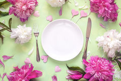 Festive table setting with cutlery,  peonies and hearts on green Stock Photos
