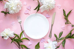 Festive table setting with cutlery, white peonies and hearts on pink table. Stock Photos