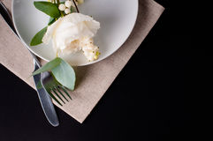 Festive table setting. With floral decoration, white roses, leaves and berries on a black background Stock Images