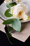 Festive table setting. With floral decoration, white roses, leaves and berries on a black background Stock Image