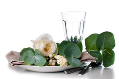 Festive table setting with floral decoration. White roses, leaves and berries on a white background Stock Photos