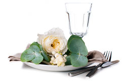 Festive table setting with floral decoration. White roses, leaves and berries on a white background Royalty Free Stock Images
