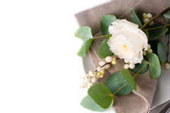 Festive table setting with floral decoration. White roses, leaves and berries on a white background Stock Photography