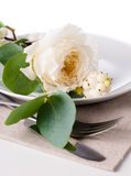 Festive table setting with floral decoration. White roses, leaves and berries on a white background Stock Images