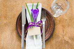 Festive Table Setting With Flower and Empty Tag. Spring Festive Table Setting With Fresh Flower and Empty Tag. Napkin, plate and cutlery on wooden table Stock Photography