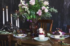 The festive table setting with flowers bouquet, candles and dessert Royalty Free Stock Photography