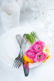 Festive table setting with flowers. Festive table setting with a bouquet of colorful buttercups flowers, vintage crockery and cutlery, wedding party, close up Stock Images