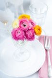 Festive table setting with flowers. Festive table setting with a bouquet of colorful buttercups flowers, vintage crockery and cutlery, wedding party, close up Stock Photo