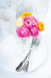 Festive table setting with flowers. Festive table setting with a bouquet of colorful buttercups flowers, vintage crockery and cutlery, wedding party, close up Royalty Free Stock Images