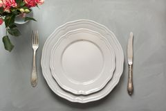 Festive table setting with flowers, vintage dishware, silverware and decorations on gray. Top view. Concept. Festive table setting with flowers, vintage Royalty Free Stock Photos
