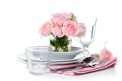 Festive table setting with pink roses. Candles and shiny new cutlery on a white background, isolated, ready template Royalty Free Stock Image