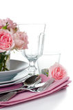 Festive table setting with pink roses. Candles and shiny new cutlery on a white background, isolated, ready template Royalty Free Stock Photography