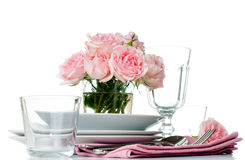 Festive table setting with pink roses. Candles and shiny new cutlery on a white background, isolated, ready template Royalty Free Stock Photo
