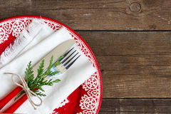 Festive table setting. With red plate on wooden background Royalty Free Stock Photo
