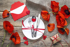 Festive table setting with red poppies, gift box and envelope on Royalty Free Stock Photos