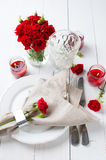 Festive table setting with red roses. And candles on white wooden table, rustic style Royalty Free Stock Photo