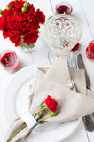 Festive table setting with red roses. And candles on white wooden table, rustic style Royalty Free Stock Photos