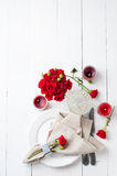Festive table setting with red roses. And candles on white wooden table, decorations on a background, rustic style Stock Images