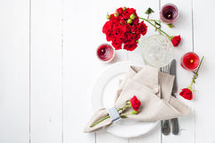 Festive table setting with red roses. And candles on white wooden table, decorations on a background, rustic style Royalty Free Stock Image