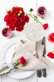 Festive table setting with red roses. And candles on white wooden table, rustic style Stock Photos