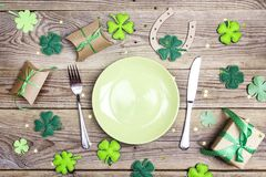 Festive table setting for St.Patrick`s day with cutlery and luck. Y symbols on wooden table. Copy space, top view Stock Images