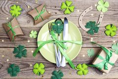 Festive table setting for St.Patrick`s day with cutlery and luck. Y symbols on wooden table. Top view Royalty Free Stock Photography