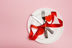Festive table setting for Valentine`s Day with fork, knife, hearts on a red background. Top view. - Image royalty free stock photos