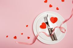 Festive table setting for Valentine`s Day with fork, knife, hearts on a red background. Top view. - Image