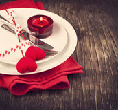 Festive table setting for Valentine's Day. With fork, knife and hearts on wooden background Royalty Free Stock Photography